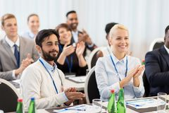 People applauding at business conference. Business and education concept - group of happy people applauding at international conference Stock Image