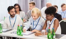 Happy business team at international conference. Business and education concept - group of people at international conference discussing papers royalty free stock image