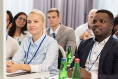 Happy business team at international conference. Business and education concept - group of people at international conference or lecture Stock Images