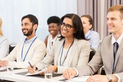 Happy business team at international conference. Business and education concept - group of people at international conference or lecture Royalty Free Stock Images
