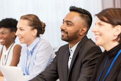 Happy business team at international conference. Business and education concept - group of people at international conference or lecture Royalty Free Stock Photography