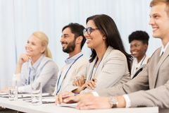 Happy business team at international conference. Business and education concept - group of people at international conference or lecture stock photos