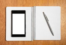 Business and education concept - smartphone and notepad Royalty Free Stock Images