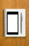 Business and education concept - smartphone and notepad Royalty Free Stock Photo