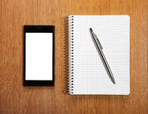 Business and education concept - smartphone and notepad Stock Image