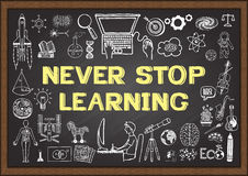 Business and education doodles with the concept of NEVER STOP LEARNING on chalkboard Royalty Free Stock Photography