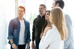 Business, education and office concept - business team with flip board in office discussing something stock image