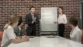 Business, education and office concept - serious business team with flip board in office discussing something stock image