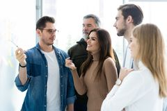 Business, education and office concept - business team with flip board in office discussing something. royalty free stock photography