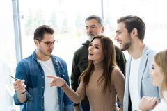 Business, education and office concept - business team with flip board in office discussing something. royalty free stock images