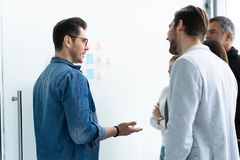 Business, education and office concept - business team with flip board in office discussing something. stock images