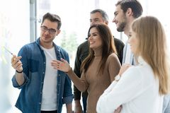 Business, education and office concept - business team with flip board in office discussing something. Business team with flip board in office discussing royalty free stock images