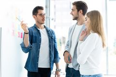 Business, education and office concept - business team with flip board in office discussing something. royalty free stock photo