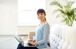 Happy asian woman with laptop computer at office. Business, education and people concept - happy young asian woman with laptop computer working at office Stock Images