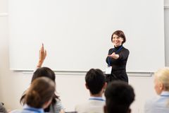 Group of people at business conference or lecture. Business, education and people concept - smiling businesswoman or teacher answering questions at conference royalty free stock photos