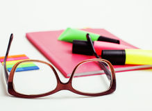 Business, education and technology concept - close up of notebook, paper stickers, glasses, pencil different new stuff. On white background macro Stock Photos