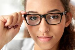 Portrait of african american woman in glasses. Business, education and vision concept - portrait of african american woman in glasses at office Stock Image