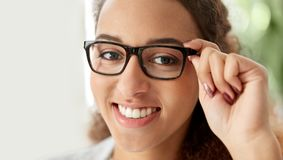 Portrait of african american woman in glasses. Business, education and vision concept - portrait of smiling african american woman in glasses at office Stock Images