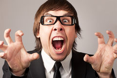 Business emotions - Anger. Stilish businessman screaming ang expressing anger. On a grey background Stock Images