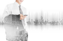 Business employee using smart phone with double exposure city in sunrise and site construction with workers, and panoramic city Royalty Free Stock Photo