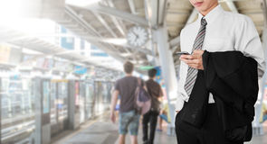 Business employee using smartphone, while waiting for BTS sky train to going office for working in rush hour morning royalty free stock images
