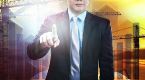 Business and engineering man pointing finger to require person t. O working with construction team against industry site background Stock Photography