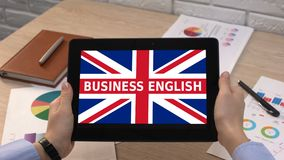 Business English app against Britain flag on tablet in female hands, tutorial. Stock footage stock video footage