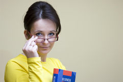 Business English teacher. A young English teacher looking from behind her glasses, friendly expression on her face. A business English book in her hands stock images