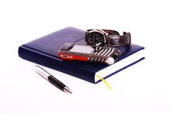 Business equipment. Notebook, watch, business model of cell phone, pen, isolated Stock Images