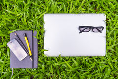 Business equipment on grass field, Top view concept Royalty Free Stock Images