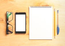 Business essentials. Top view of spiral blank notebook. Business essentials. Top view of spiral blank notebook and smartphone on wood desk background Royalty Free Stock Photos