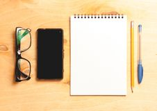 Business essentials. Top view of spiral blank notebook. Business essentials. Top view of spiral blank notebook and smartphone on wood desk background Stock Photos