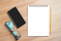 Business essentials. Top view of spiral blank notebook. Business essentials. Top view of spiral blank notebook and smartphone on wood desk background Stock Images
