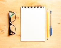 Business essentials. Top view of spiral blank notebook. Business essentials. Top view of spiral blank notebook on wood desk background Royalty Free Stock Photo