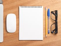 Business essentials. Top view of spiral blank notebook. Business essentials. Top view of spiral blank notebook on wood desk background Stock Images