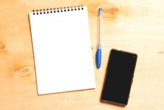 Business essentials. Top view of spiral blank notebook. Business essentials. Top view of spiral blank notebook and smartphone on wood desk background Royalty Free Stock Photo