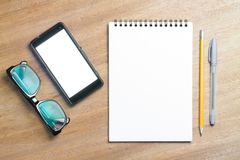 Business essentials. Top view of spiral blank notebook. Business essentials. Top view of spiral blank notebook and smartphone on wood desk background Stock Image