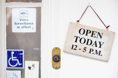 Business establishment with `Open Today` sign. Business establishment or store with its hours of operation sign hanging outside their door with other different stock image