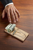 Business Trap Money Ethics Bribe. A conceptual image of a businessmans hand reaching in to grab American money set in a mouse or rat trap Stock Photography