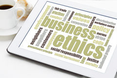 Business ethics word cloud. On a digital tablet with a cup of coffee stock images