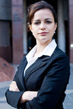 Business executive. Close up portrait of a young confident beautiful female executive smiling with her arms crossed, background is a corporate building with blue Royalty Free Stock Photos