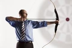 Business executive aiming at target.