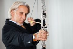 Business executive aiming at target. Male business executive aiming at target with bow and arrow Royalty Free Stock Photography