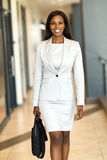 Business executive with briefcase. Cheerful african american business executive with briefcase in office building stock photos