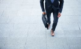 Business executive with briefcase going up the stairs. Royalty Free Stock Photo