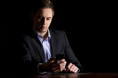Business executive checking text messages. Handsome young businessman in dark suit sitting at office desk reading text messages on mobile-phone, low-key image Stock Images