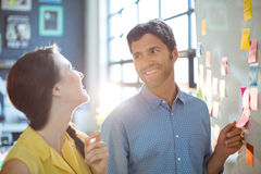 Business executive and co-worker interacting while looking at sticky notes on whiteboard. In office Stock Photography