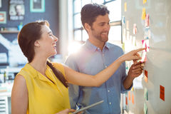 Business executive and co-worker interacting while looking at sticky notes on whiteboard Stock Images