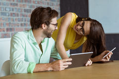 Business executive and co-worker interacting while using digital tablet Stock Images