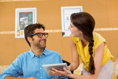 Business executive and co-worker interacting while using digital tablet Royalty Free Stock Photography